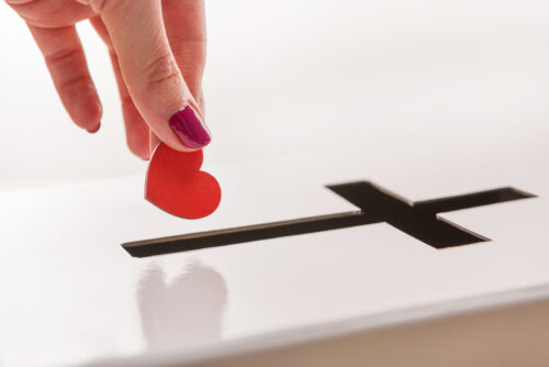 Close-up partial view of woman inserting red heart symbol into hole for donations in form of cross, donation and faith concept
